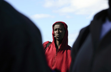 A would-be immigrant smokes upon arriving at the port after being intercepted in Spain
