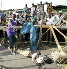 The body of a dead man lays before being covered by an onlooker in a street of Adjame.