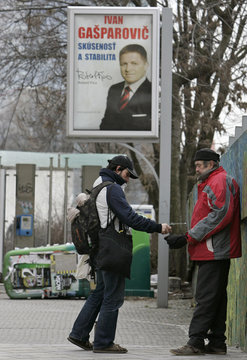 A man gives money to a beggar near a poster which shows Slovakia's Prime Minister Robert Fico in Bratislava