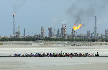 Aerial view of the pack of riders cycling past a chemical plant during the 3rd stage of the Tour of Qatar