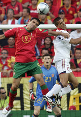 PORTUGAL'S PAULETA AND SPAIN'S JUANITO JUMP FOR THE BALL IN THEIR EURO 2004 MATCH IN LISBON.