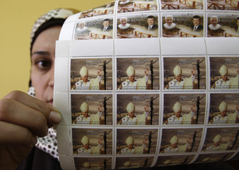 Postal worker displays sheets of stamps with images of Pope Benedict XVI and Jordan's King Abdullah at a post office branch in Amman