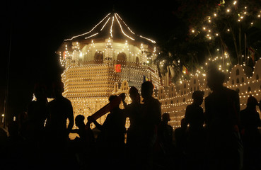 Torchbearers get ready near the tooth temple during the annual Esala cultural pageant in Kandy