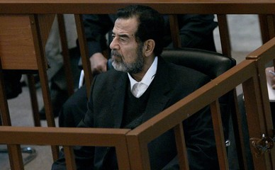 Saddam Hussein looks at pictures of murdered Kurdish Iraqis during the continuation of his 'Anfal' genocide trial in Baghdad