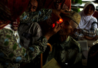 An elderly man has his eye examined by a paramedic as part of a joint initiative offering free cataract surgery for the poor at a hospital in Tangerang