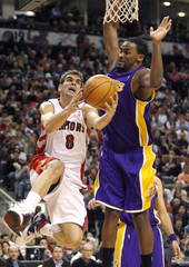 Raptors guard Calderon goes to the basket against Lakers' Turiaf during the first half of their NBA basketball game in Toronto