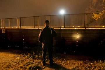 Member of Mexican immigration group Beta checks border wall between Mexico and United States during patrol in Tijuana