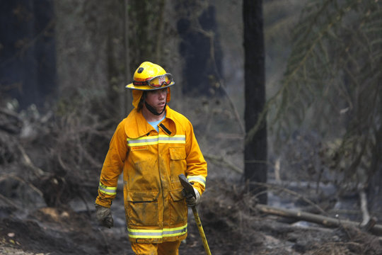 A firefighter holds an axe while working to extinguish the remnants of a bushfire on the outskirts of Healsville