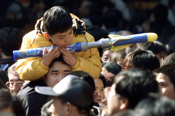 CHINESE BOY HOLDS ON TO HIS TOY ROCKET IN SHANGHAI.