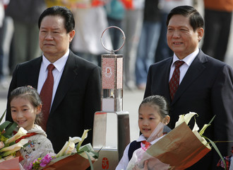China's Politburo Standing Committee Member Zhou and president of Beijing Olympics organizing committee Liu stand behind the Olympic flame in Beijing airport