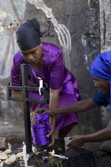 A Voodoo believer prays over a tomb in a cemetery during one of their ceremonies in Port-au-Prince