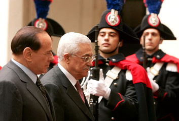 Italian Prime Minister Berlusconi and Palestinian President Abbas review an honour guard before a meeting in Rome