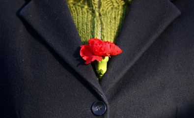 A woman  carries a carnation at the Monument for the Socialists during the traditional ceremony to mourn the deaths of German communist leaders Karl Liebknecht and Rosa Luxemburg in Berlin