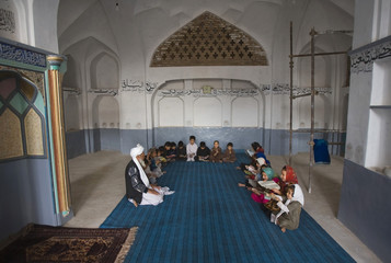 Afghan children read from the Koran as they attend a traditional Koran school held in an old synagogue being used as a Muslim mosque in Herat