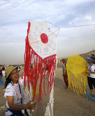 Maeda from Japan, member of the Follow Women Foundation, prepares to release kite depicting a Japanese flag with peace messages on it after arriving at Amman Citadel