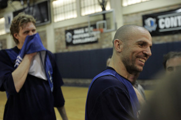 Mavericks guard Kidd talks with the media as forward Nowitzki watches after a basketball practice session in Dallas