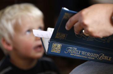 Joshua Jeub, 3, looks at his father Chris holding a bible during a worship gathering in the family home in Monument