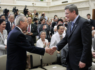 Canadian Prime Minister Harper greets former head tax payer James Pon during a ceremony in Ottawa