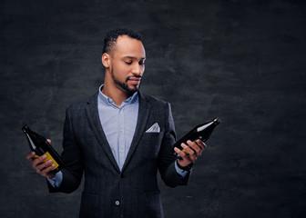 Studio portrait of elegant black male in a suit holds beer bottles.