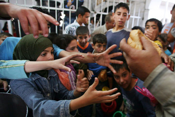 Palestinian kids receive food at soup kitchen in Old city in West Bank city of Hebron