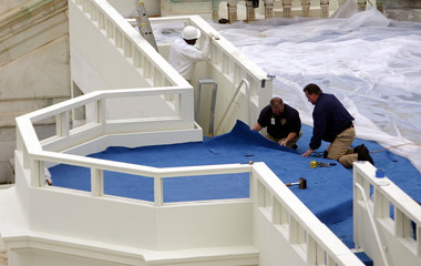 Workmen lay carpet as they prepare podium for inauguration in Washington.