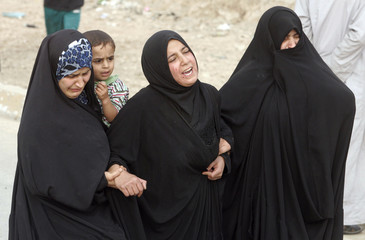 Mourners cry during a funeral for residents killed during clashes in Baghdad's Sadr City