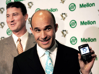 New Pittsburgh Penguins owner Jim Balsillie holds up a Blackberry with the team's logo on the screen while former Penguins star Mario Lemieux laughs in the background in between periods of the Penguins NHL game with the Flyers in Pittsburgh