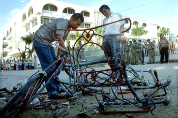 INDONESIAN OFFICERS CHECK A WRECKED PEDICAB AFTER AFTER A BOMB EXPLODED OUTSIDE A CHURCH IN MEDAN.