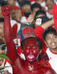 A supporter of the Indonesia Democratic Party - Struggle, whose body is painted with the party's colour of red, chants a slogan during rally in Surabaya