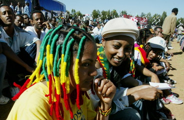 Young Ethiopian girls who have braided their hair with rasta colours, sit among thousands of people ..