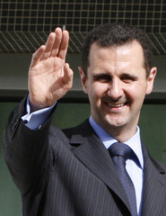 Syria's President al-Assad waves to the crowd from the presidential place after his victory in a referendum in Damascus