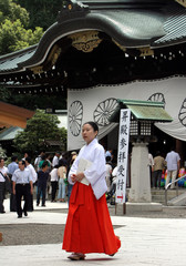 Shrine maiden walks past Yasukuni Shrine, a shrine for war dead seen by many in Asia as symbol of Japan's past militarism, in Tokyo