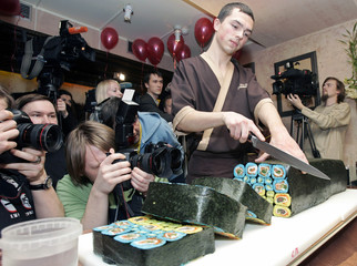 Photographers take pictures of a gigantic sushi roll at Japanese restaurant in Kiev