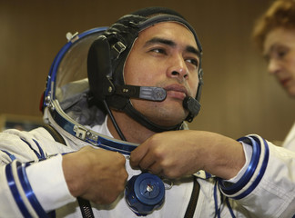 Malaysian cosmonaut Sheikh Muszaphar Shukor gestures as he tries on a space suit at the Star Corporation space outfitter outside Moscow