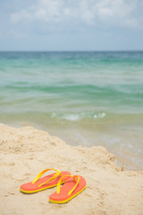 Sandals on the beach, summer holiday vacation concept. Orange sandals with turquoise sea in the background with cloudy sky.