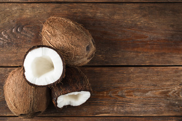Ripe fresh coconuts on wooden rustic table background, flat lay with copy space. Exotic tropical fruits.