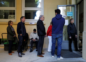 People wait in line before the opening of a polling station for the second round of 2017 French presidential election at a polling station in Marseille