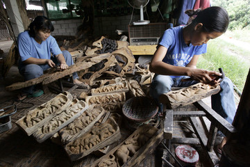 Workers carve wood in a village in the northern Thai town of Chiang Mai province