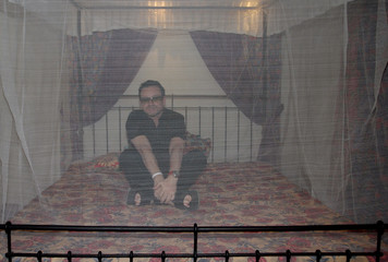 Irish U2 lead singer and anti-poverty campaigner Bono sits in a bed covered with a treated mosquito net in Arusha