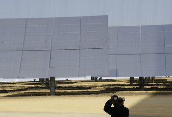 A photographer takes pictures in front of solar panels at a soon-to-be completed solar park at Sanlucar La Mayor, near Seville