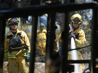 A firefighter sprays water on the rubble of a house that burned during the Jesusita fire in Santa Barbara