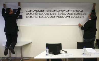 Two members of the Swiss bishop - conference hang-up a logo before a news conference in Bern