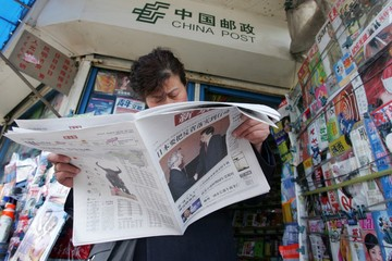 A Chinese woman reads an issue of the Beijing News at a newsstand in Beijing.