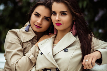 Two beautiful twins young women in trench coats near blooming lilac