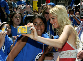 Actress Lindsay Lohan takes a picture with a fan at the World Premiere of Herbie Fully Loaded in Hollywood.