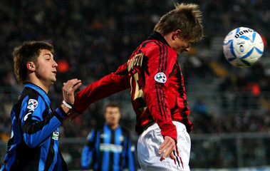 AC Milan's Tomasson challenges Capelli of Atalanta during their Serie A match in Bergamo.