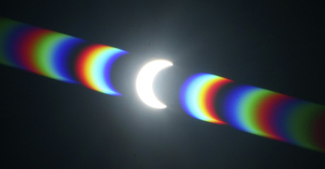Light is diffracted on a filter during a partial solar eclipse, where the moon moves between the sun and earth, as seen from Cape Town