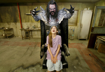 "British actress Skye Bennett and Finnish musician Tomi Petteri Putaansuu, dressed as his character of ""Mr Lordi"", pose on the set of the horror movie ""Dark Floors"" in Oulu"