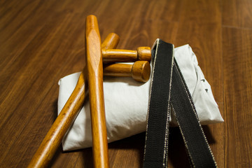 Tonfa ( traditional okinawan karate's weapon) , black belt and Gi (japanese martial arts uniform) on the floor
