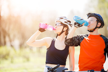 Cyclists drink water from bottle